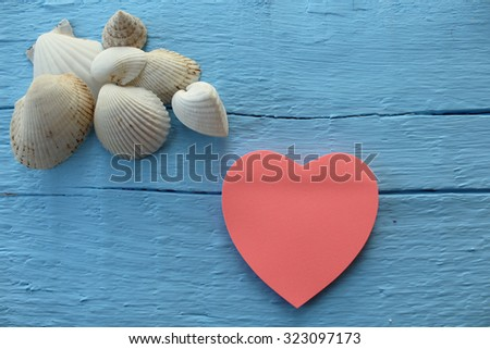 Blank paper note with heart shape on grunge blue wooden background with copy space - stock photo
