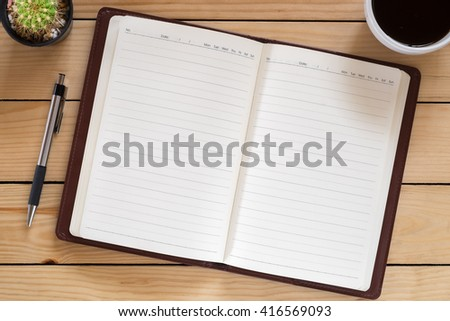 Blank paper notebook with pen and cup of coffee on wooden table.Working desk concept.Leather notebook on desk table.Pencil on desk table.Brown color cover leather notebook.Writing notes. - stock photo