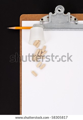 Blank Paper on Clipboard with Pencil and Pills - stock photo