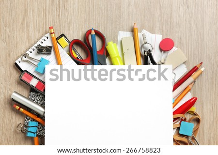 Blank paper on lots of office supplies - stock photo