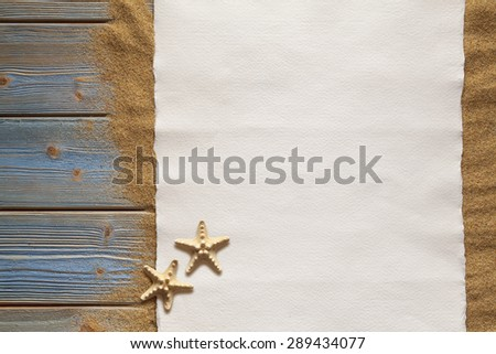 Blank paper sheet and two starfish on planks and sand - stock photo
