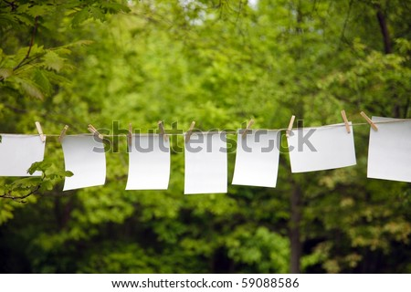 blank paper sheet hanging on a rope outdoor - stock photo
