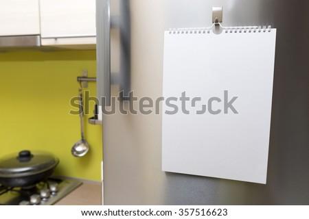 blank paper sheet hanging on fridge door - stock photo