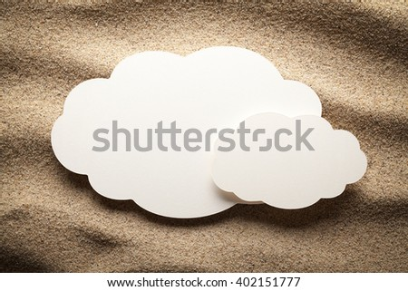 Blank paper sheet in the shape of cloud on sand - stock photo