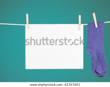 blank paper sign hanging from a clothesline next to a purple sock. - stock photo