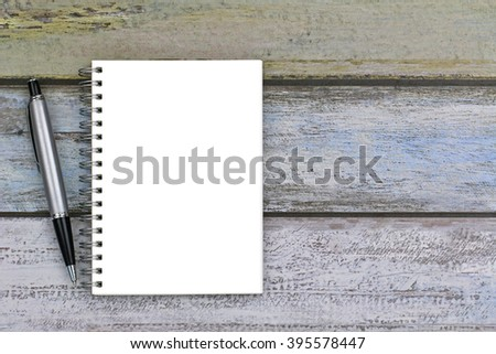 Blank paper spiral ring notebook with a silver pen on blue green wooden looking tile and copyspace