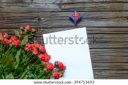 Blank paper with copy space on top of wooden surface beside large bundle of pink roses and blue gift box wrapped with red ribbon - stock photo