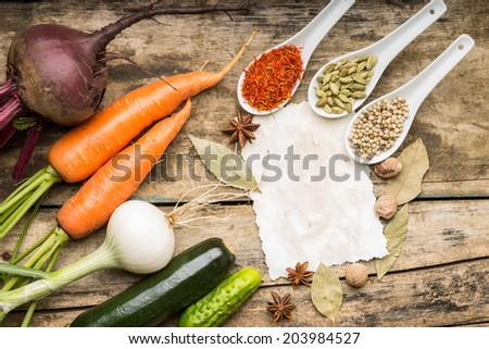 Blank paper with fresh vegetables and various of spices on wood background. Top view. - stock photo