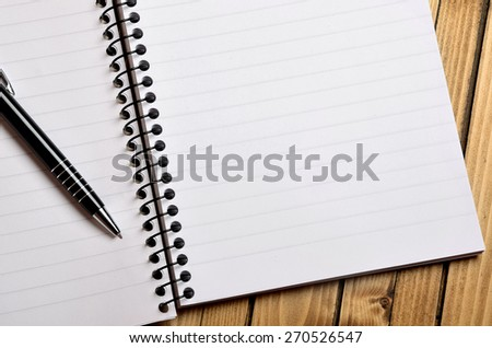Blank paper with pen on table - stock photo
