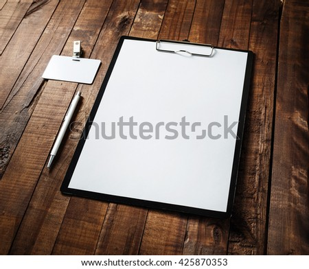 Blank paperwork template. Clipboard with blank white paper, letterhead, pen and badge on vintage wooden table background. Responsive design mock-up. Blank stationery set. - stock photo