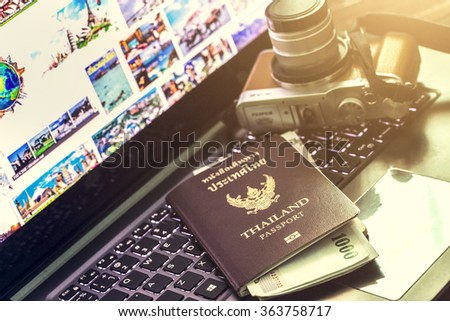 Blank passport and camera with US dollars on wood table - stock photo