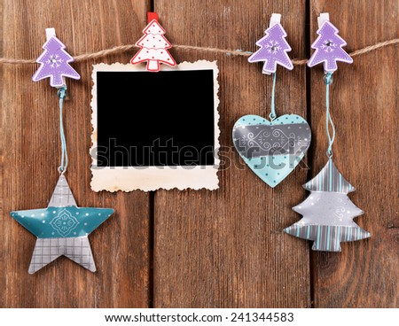 Blank photo frame and Christmas decor on rope, on wooden background - stock photo