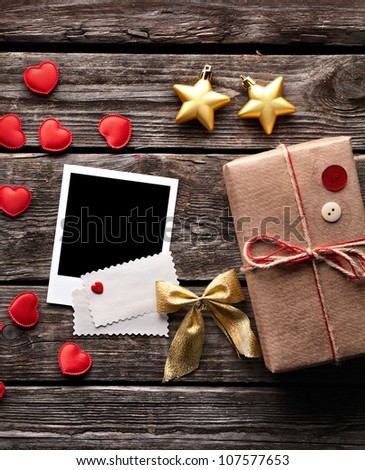 Blank photo frame and vintage gift box (package) with blank gift tag on old wood. Lovely christmas background. - stock photo