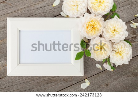 Blank photo frame and white roses over wooden table background - stock photo