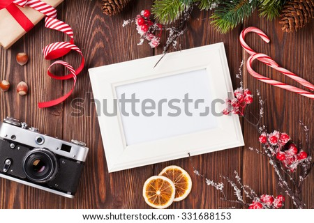 Blank photo frame with christmas gift box, pine tree and camera on wooden table. Top view - stock photo