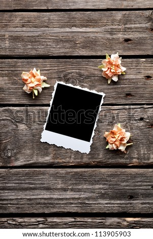 Blank photo frame with dried flowers on old wooden background. - stock photo