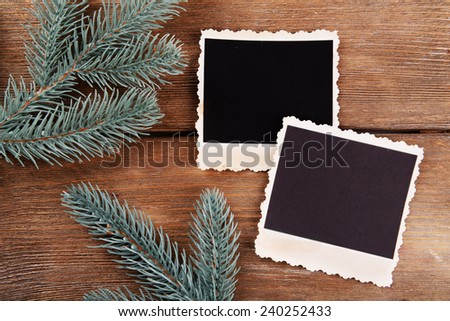 Blank photo frames and fir tree on wooden table background - stock photo