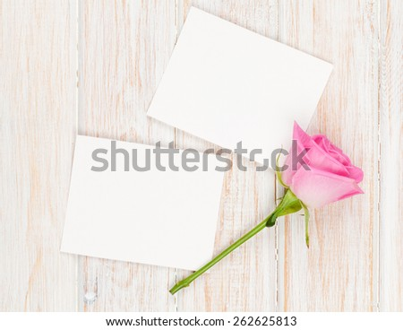 Blank photo frames and pink rose over wooden table. Top view with copy space - stock photo