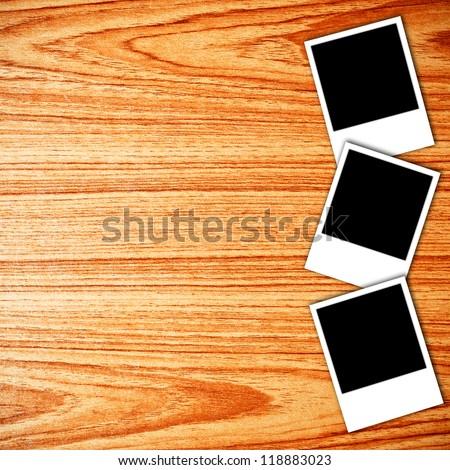 Blank photo frames on wood background - stock photo