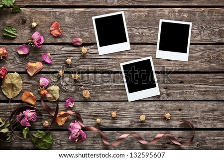 Blank photo frames with rose petals and dried flowers on old wooden plates. - stock photo