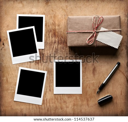 Blank photo frames with vintage gift box and tag on old wooden background. - stock photo