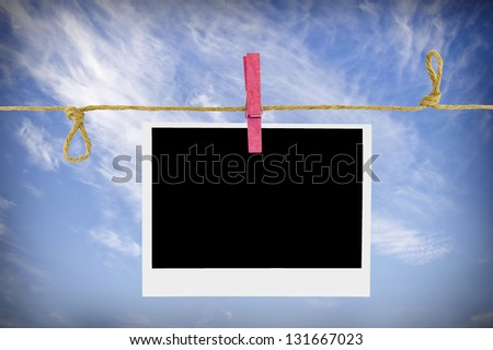Blank photos hanging on a clothesline against a blue sky - stock photo