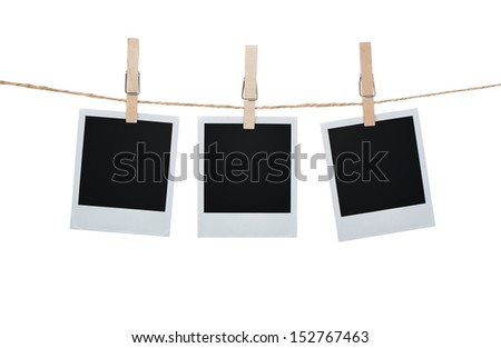 Blank photos hanging on a clothesline isolated on white background with clipping path for the inside of the frames - stock photo