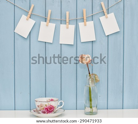 Blank photos hanging on rope with clothespins on blue wooden background, cup of tea and rose - stock photo