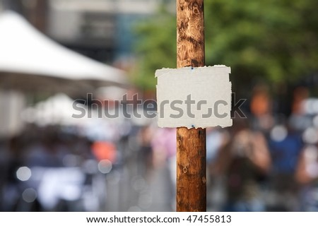 Blank piece of cardboard nailed on electric wooden pole - stock photo