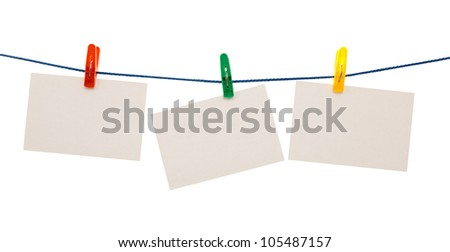Blank pieces of paper and colored clothespins isolated on white - stock photo