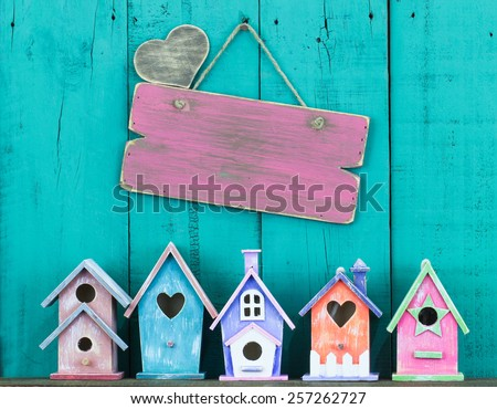 Blank pink wood sign with heart and row of birdhouses hanging on antique teal blue wooden background - stock photo
