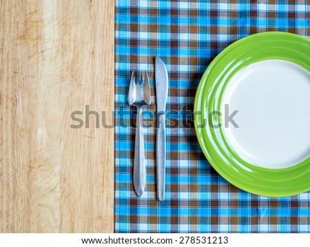 Blank plate with fork and knife on checked tablecloth and wooden table background - stock photo