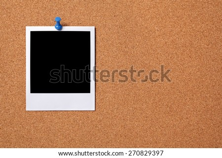 Blank polaroid photo print, pushpin, cork background.  Copy space - stock photo