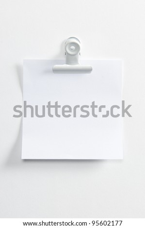 Blank post hanging on the wall with a forceps - stock photo