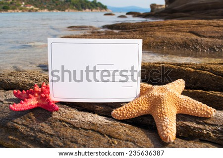 Blank postcard between starfishes on the rocks - stock photo