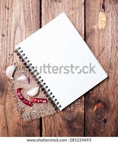 blank recipe book with fresh herbs and spices on wooden background - stock photo