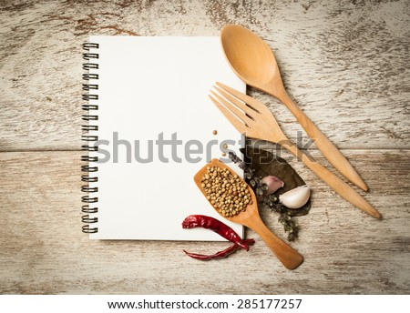 blank recipe book with wooden spoon and fresh herbs and spices on wooden background - stock photo