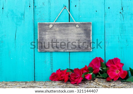 Blank rustic sign hanging on antique teal blue fence by red flowers on log border - stock photo