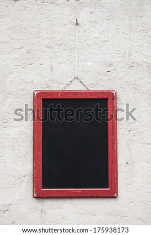 Blank school chalkboard, hanging on a wall. - stock photo