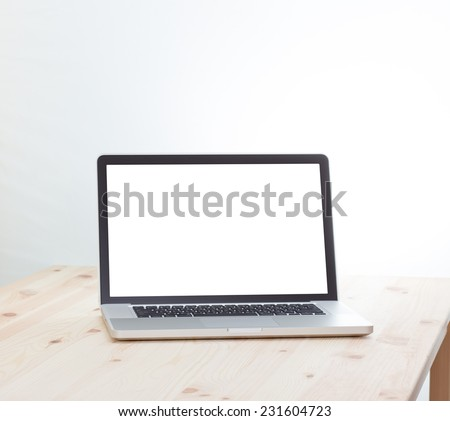 Blank screen laptop computer on wood table - stock photo