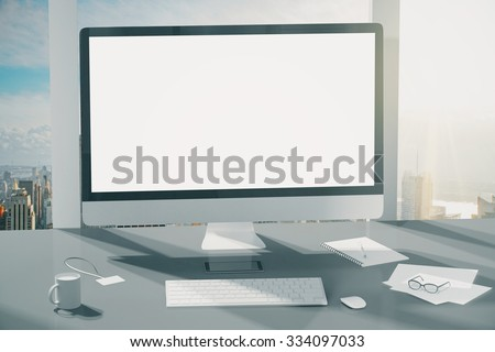 Blank screen of computer monitor, keyboard, cup of coffee and glasses on grey table, mock up - stock photo