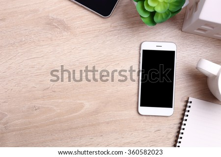 Blank screen smartphone and office supplies on wooden background - stock photo
