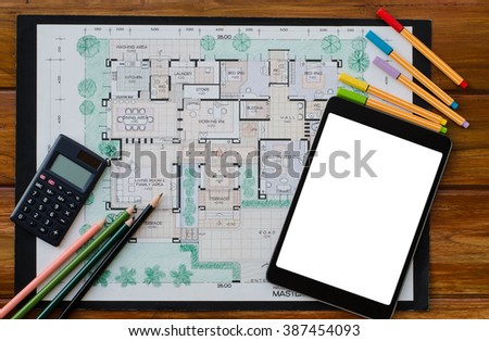 Blank screen tablet computer, calculator and drawing set on house master plan on wooden office desk, architecture workplace, top view. - stock photo