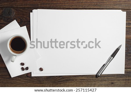 Blank sheet of paper and a cup of coffee on dark wooden table, top view - stock photo