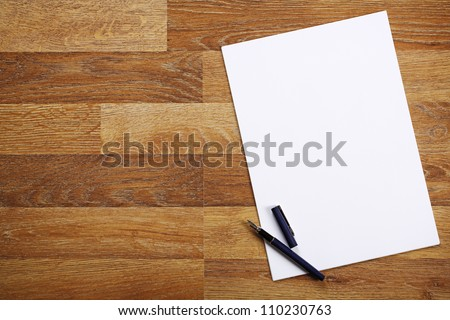 Blank sheet of paper and pen on bright wooden office desk. - stock photo