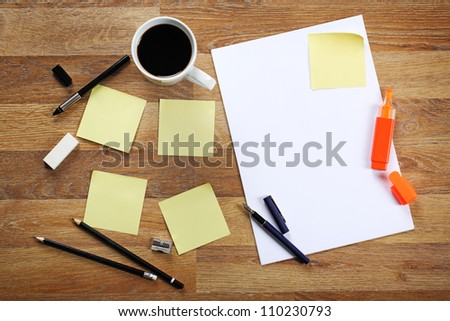 Blank sheet of paper, yellow sticky notes, cup of black coffee, pencil and pen on wooden office desk. - stock photo