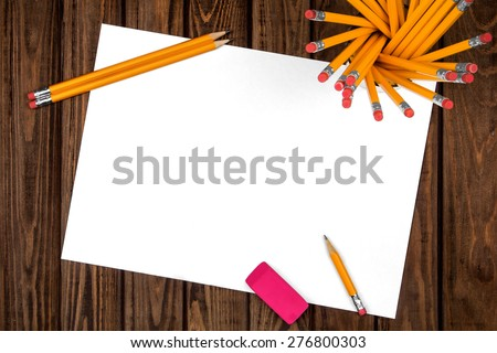 blank sheet with a pencil and an eraser on a wooden background - stock photo