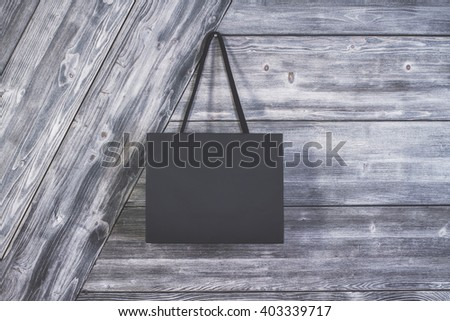 Blank shopping bag suspended on wooden wall. Mock up - stock photo