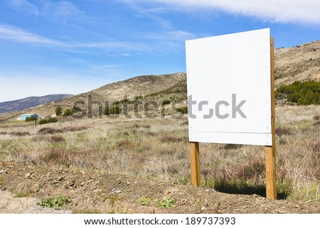 Blank sign posted in a rural scene.  - stock photo