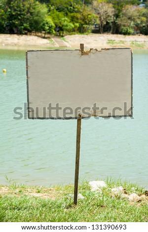 blank signboard beside lake - stock photo